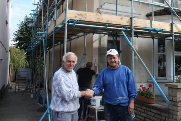 householder and contractor shake hands